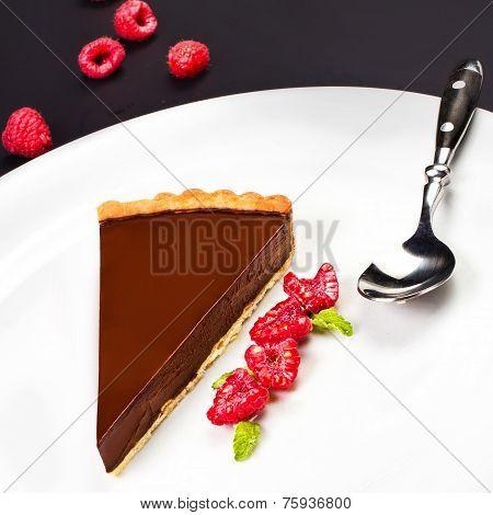 Chocolate Dessert With Raspberry. Dark Chocolate Cake With Chocolate Sauce On A White Plate, Macro