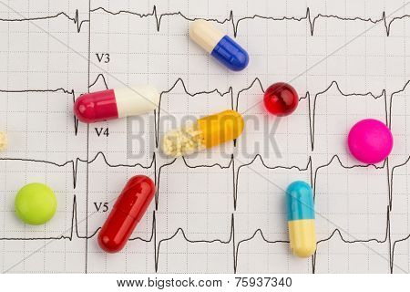 several tablets are on an ekg. photo icon for diseases of the heart and circulation