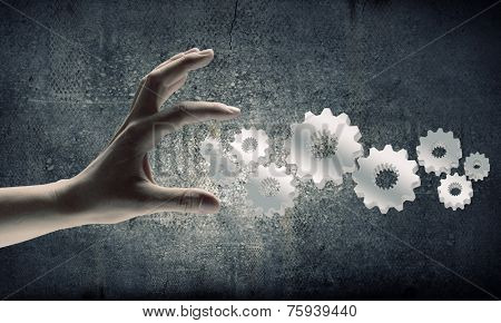 Close up of businesswoman hand and cogwheel mechanism
