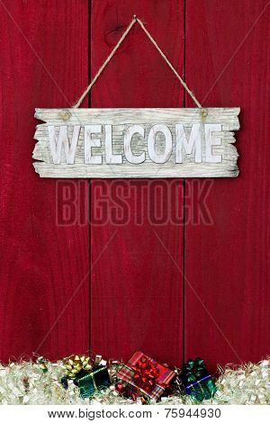 Wood welcome sign with Christmas garland and gifts border hanging on antique red wooden background