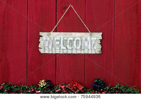 Wood welcome sign with Christmas presents and antique red wooden backgound
