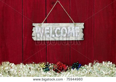 Wood welcome sign with white garland Christmas border hanging on antique red wooden background