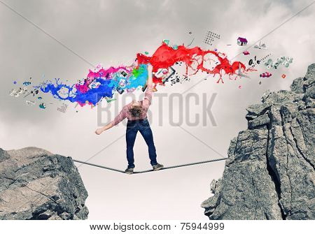 Young guy in casual evading from colorful paint splashes