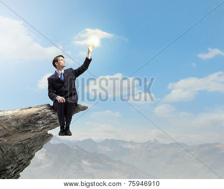 Young businessman sitting on edge of rock