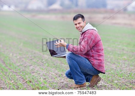 Man With Laptop In The Field