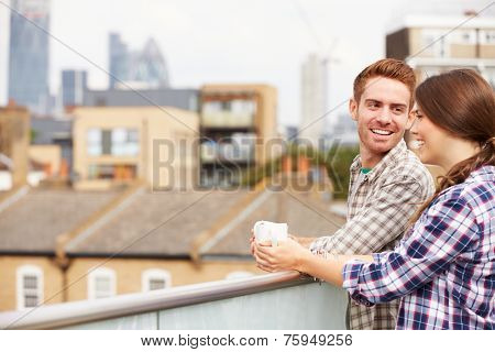 Couple Relaxing Outdoors On Rooftop Garden Drinking Coffee