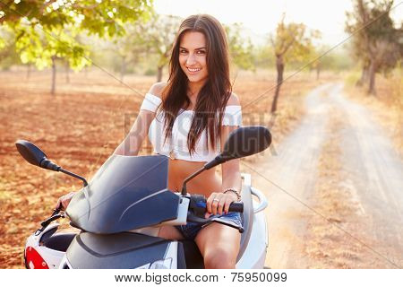 Young Woman Riding Motor Scooter Along Country Road