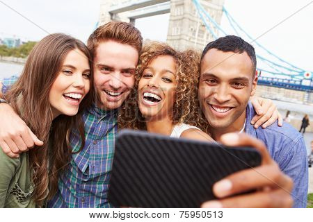 Group Of Friends Taking Selfie By Tower Bridge In London