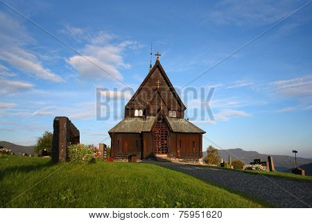 Front view of Reinli stave church, Sør-Aurdal, Norway, on a clear, bright sky.