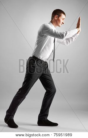 businessman pushing invisible obstacles