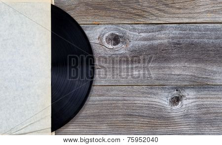 Original Vinyl Music Record In Paper Holder On Aged Wood