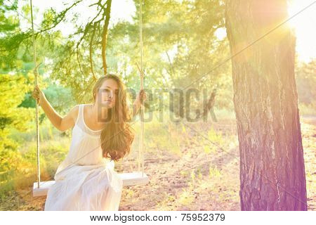 Young woman is swinging on a swing in summer pine forest. Image toned and noise added. High key.
