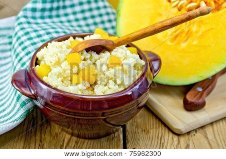 Porridge millet with pumpkin and wooden spoon