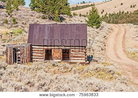 Log Home Beside A Dirt Road