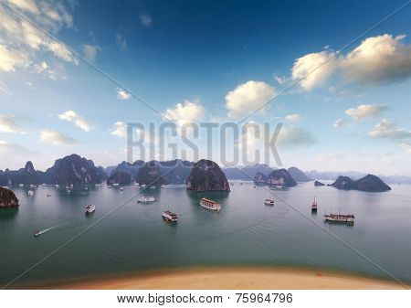 Halong Bay Vietnam. Boats, junks and tourist ships cruise. Holiday vacation destination background. Sandy beach, islands and blue sky with clouds