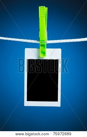 blank photo hanging on rope, blue background