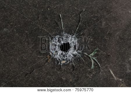 Bullet hole in glass on dirty grungy black background