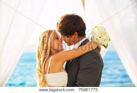 Beautiful Wedding by the Sea. Attractive Bride and Groom Embracing. Just Married on Wedding Day