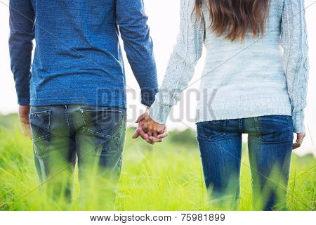 Happy Young Couple Having Fun Outdoors. Holding Hands In the Countryside on Romantic Date.