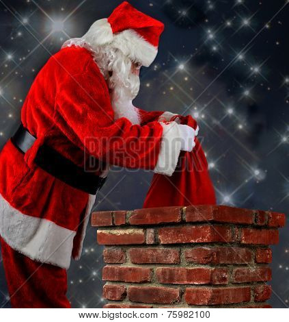 Closeup of Santa Claus placing his bag of toys into a chimney. Vertical format over a starry nightime background.