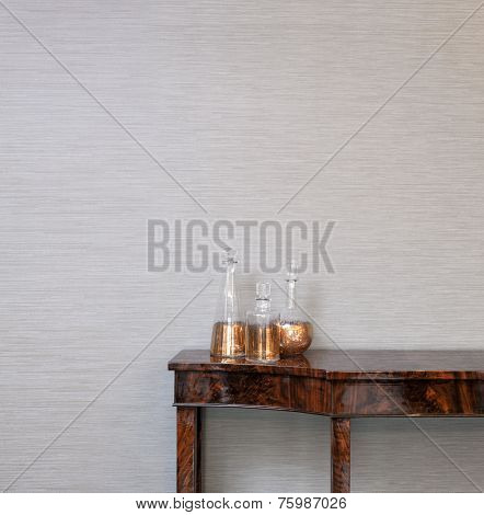 Sideboard In Front Of A Grey Wall With Whiskey Bottle