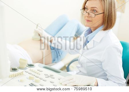 Experienced obstetrician making an ultrasound examination to pregnant woman