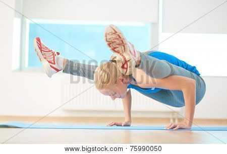 Agile blond girl standing on arms with her legs on forearms