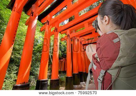 Asian female backpacker take photo in Fushimi Inari Taisha, Japan.