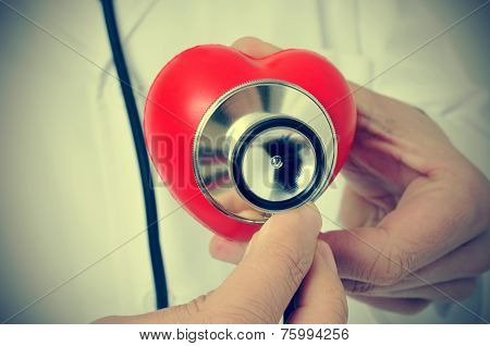 a doctor auscultating a red heart with a stethoscope, with a retro effect