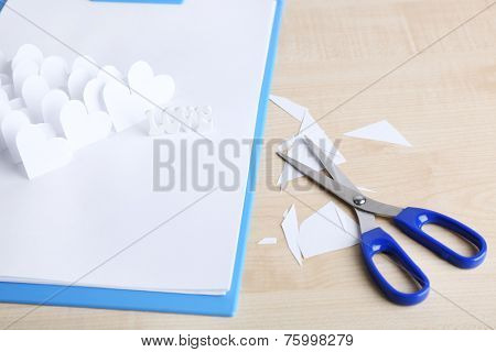 Beautiful applique paper with hearts  and scissors on table