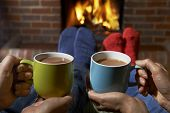 stock photo of hot couple  - Couple With Hot Drink Relaxing By Fire - JPG