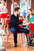 picture of diners  - Friends or couple eating fast food and drinking milk shakes on bar in American fast food diner - JPG