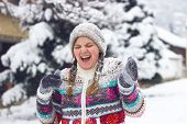 stock photo of snowball-fight  - Portrait of a happy young woman in the middle of a snowball fight on a snowy winter day