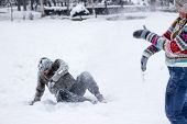 foto of snowball-fight  - Cute young hipster couple covered in snow in the middle of a snowball fight - JPG