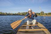 stock photo of collins  - senior male enjoying morning sun on a lake in a canoe - JPG