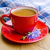 stock photo of chicory  - Chicory drink in a red cup with flower and napkin on a wooden boards background - JPG