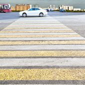 pic of zebra crossing  - yellow and white crossing zebra of pedestrian crosswalk on urban street