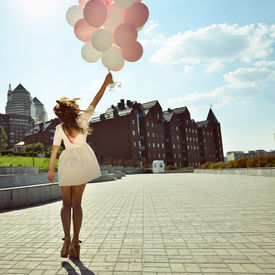 stock photo of latex woman  - Happy young woman is whirling in park over city background and holding air balloons - JPG