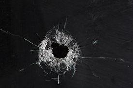 foto of gunshot  - bullet holes in glass isolated on black - JPG