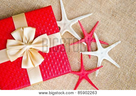 red gift box with gold ribbon and star fish on sack background