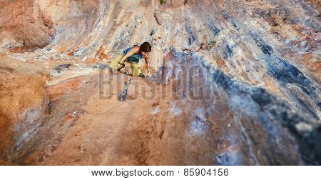 Rock climber climbing up a cliff
