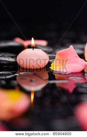 Reflection of rose petals with pink candle and therapy stones