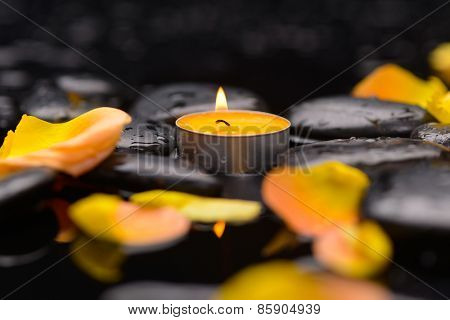 Still life with Orange rose petals with candle and therapy stones