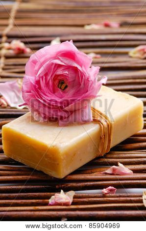 rose petals with rose on soap on  mat