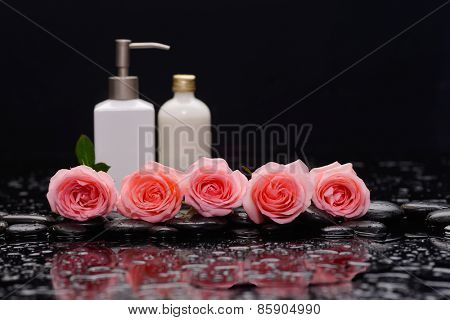Still life with pink five rose and massage oil on wet stones