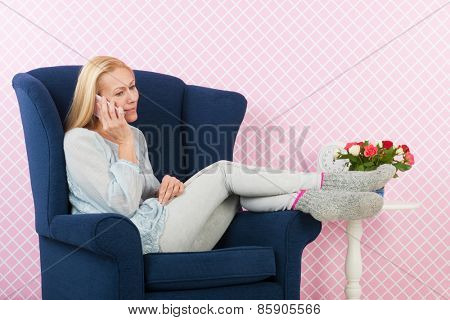 Woman of mature age on the phone in interior