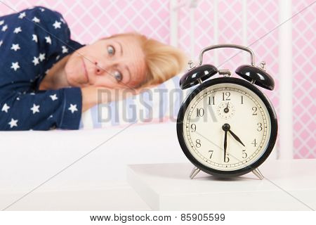 Blond woman of mature age with insomnia and big alarm clock - focus point on clock