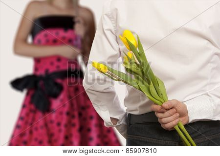 Man hiding bouquet of flowers tulip behind his back