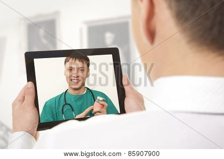 Man having video chat with doctor on laptop at home