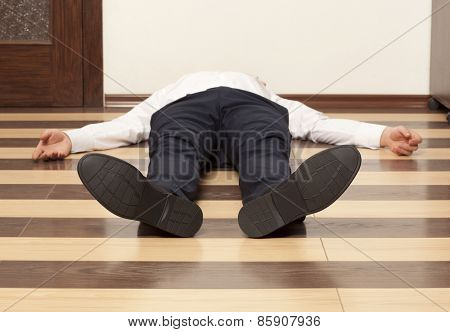 Drunkard. Young exhausted businessman lying on the floor